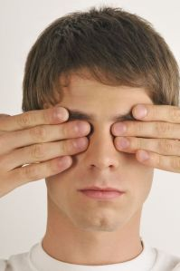 man covering eyes