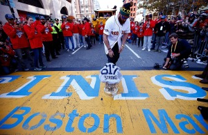 Jonny Gomes #5 of the Boston Red Sox lays the World Series trophy and the 'Boston Strong 617' jersey onto the finish line of the Boston Marathon on Boylston Street during the World Series victory parade on November 2, 2013 in Boston, Massachusetts.  (Jared Wickerham/Getty Images)