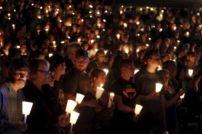 People take part in candlelight vigil following a mass shooting at Umpqua Community College in Roseburg Oregon